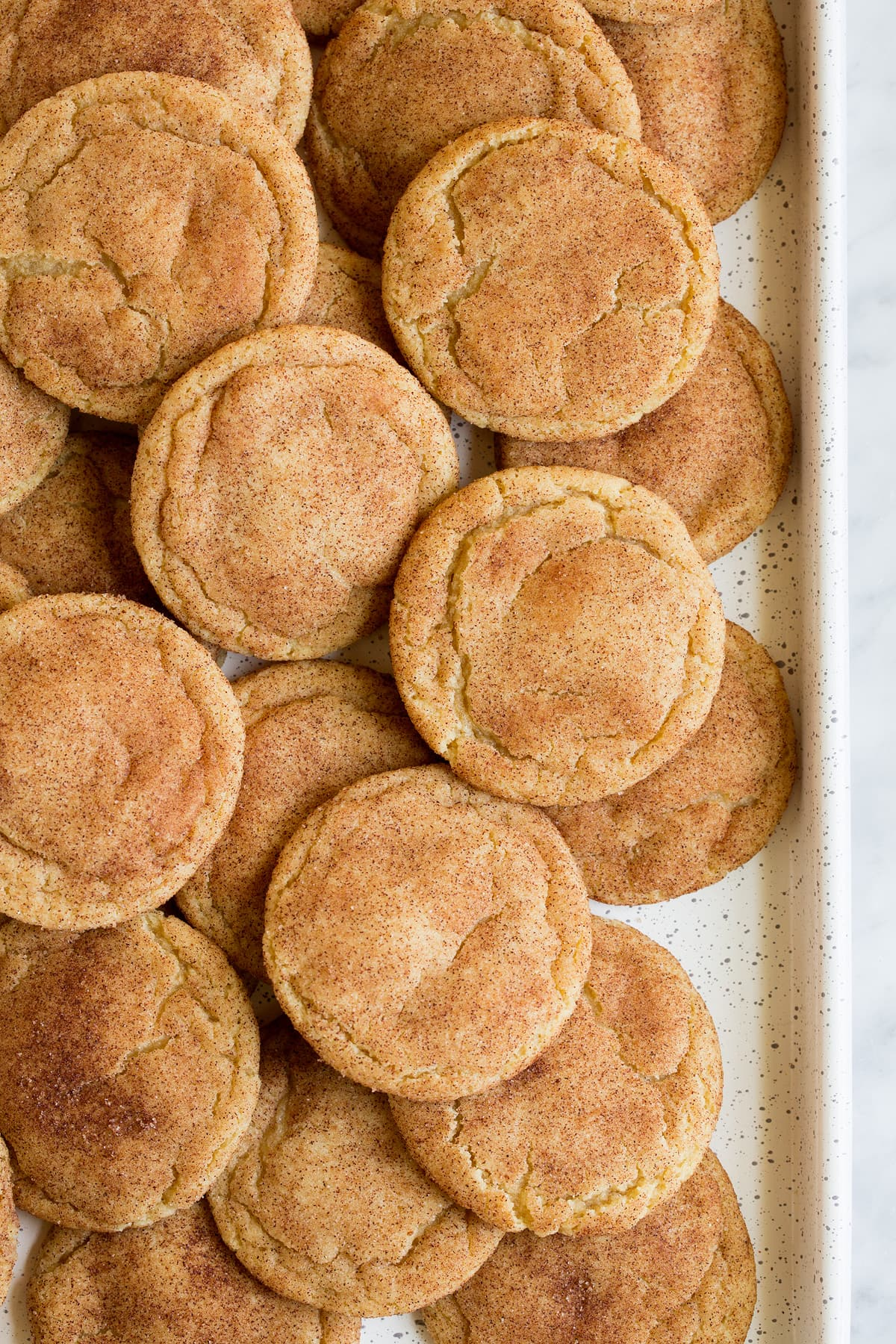 Overhead image of a white cookie sheet layered with snickerdoodle cookies.