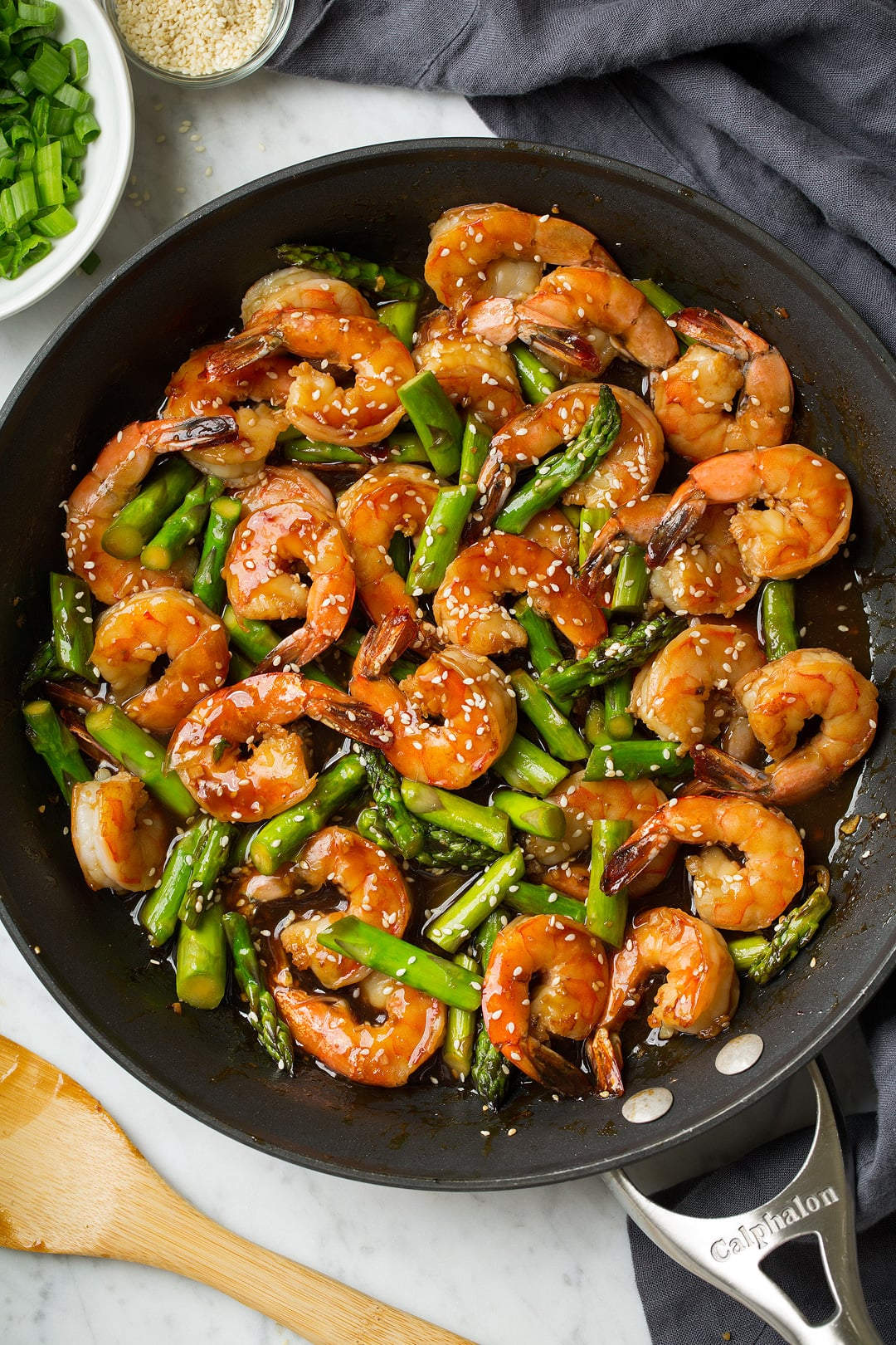 teriyaki shrimp and asparagus in a metal skillet with wooden spoon