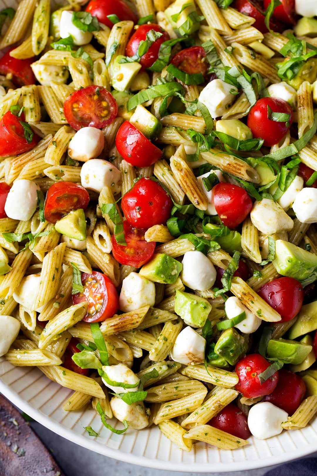 close up of Avocado Caprese Pasta Salad in white bowl