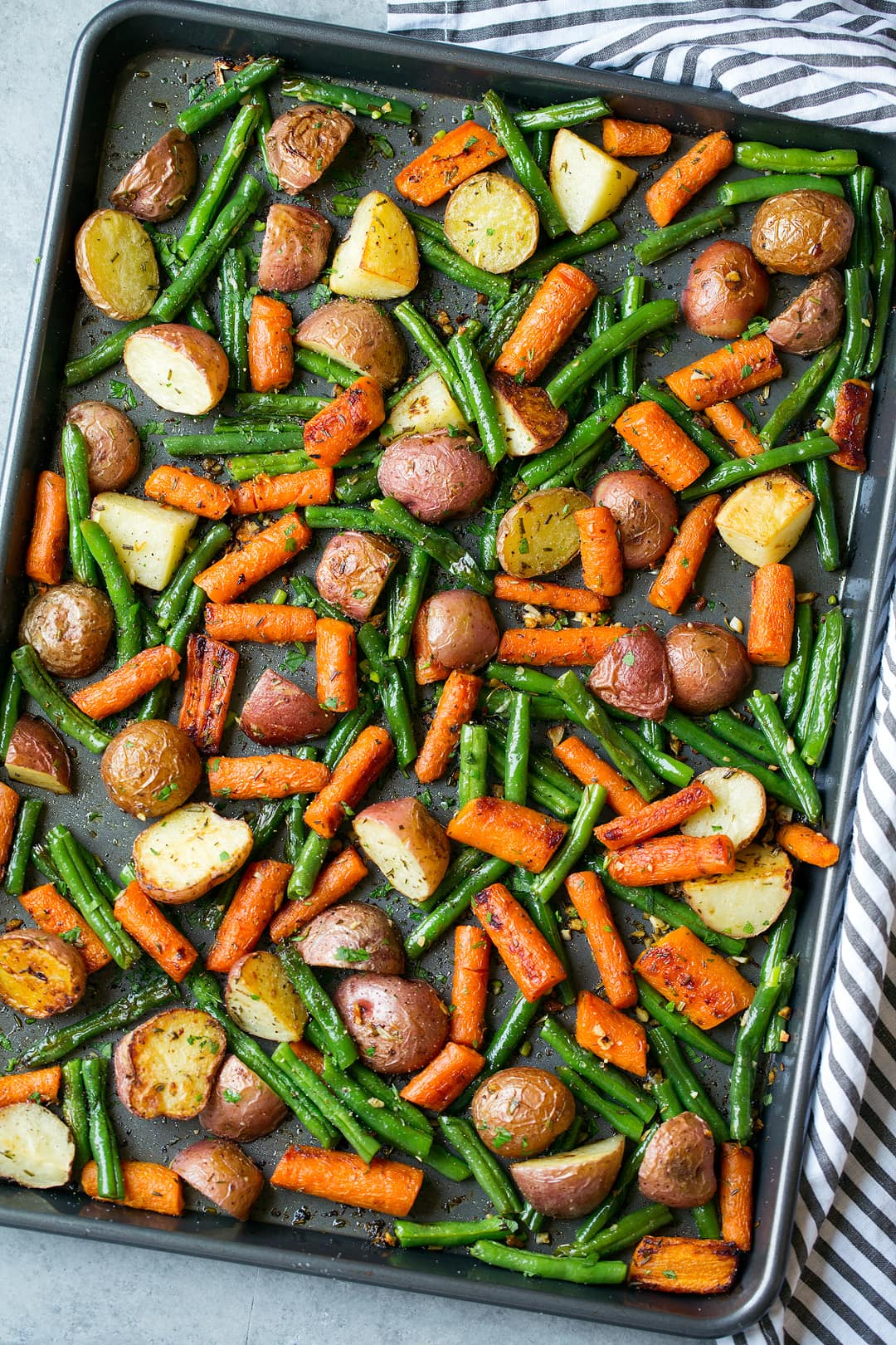 Roasted Vegetables including potatoes carrots and green beans with garlic herb seasoning. Shown here on a dark sheet pan after roasting.