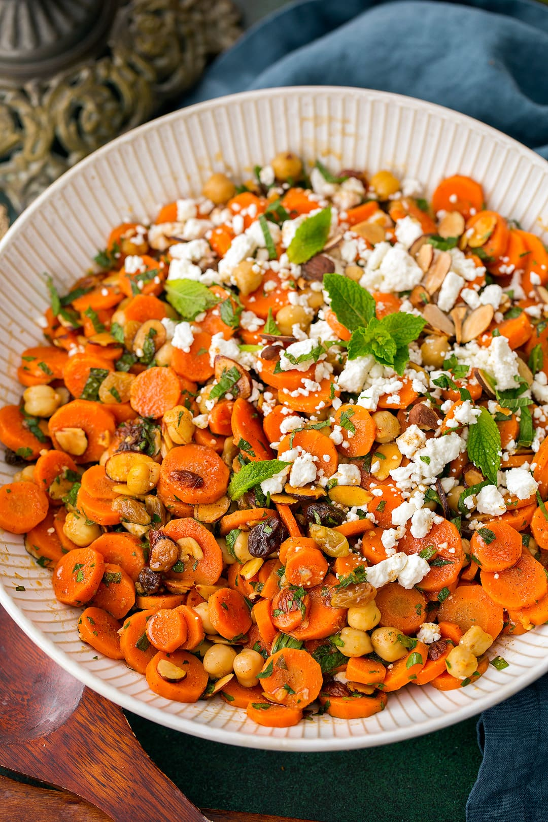 Carrot Salad with chick peas, feta, almonds and raisins. Shown here in a large white shallow bowl.