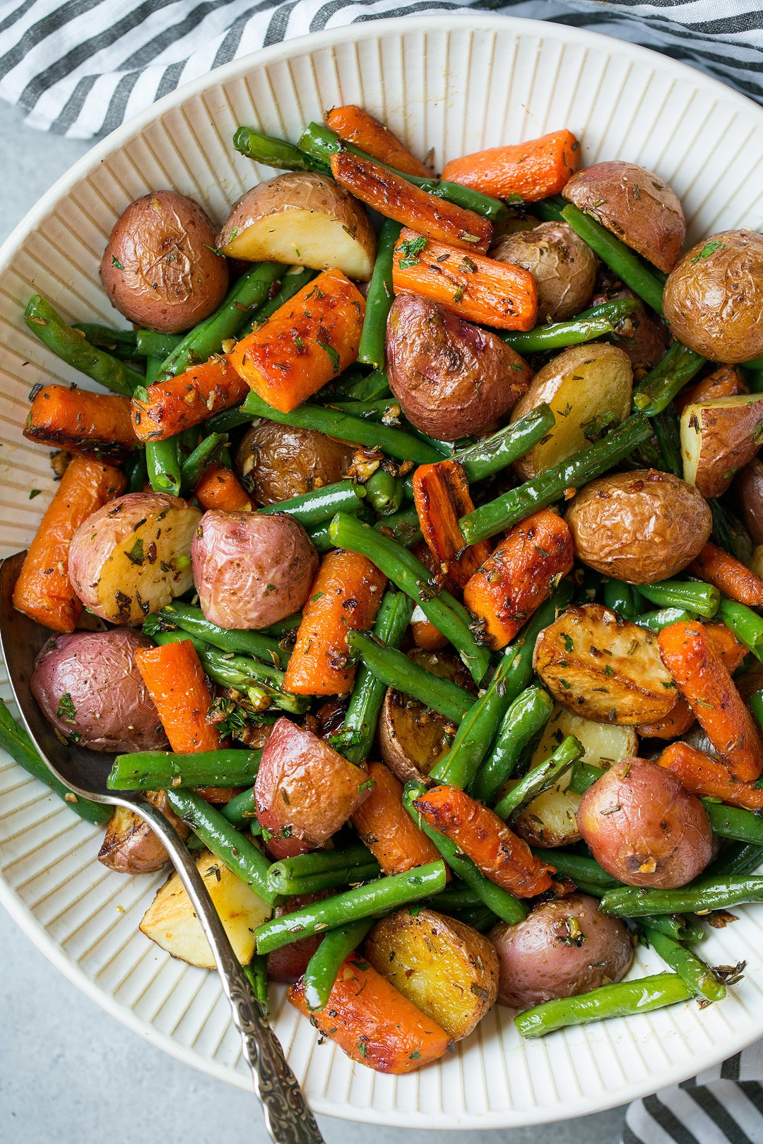 Roasted Vegetables including potatoes carrots and green beans with garlic herb seasoning.