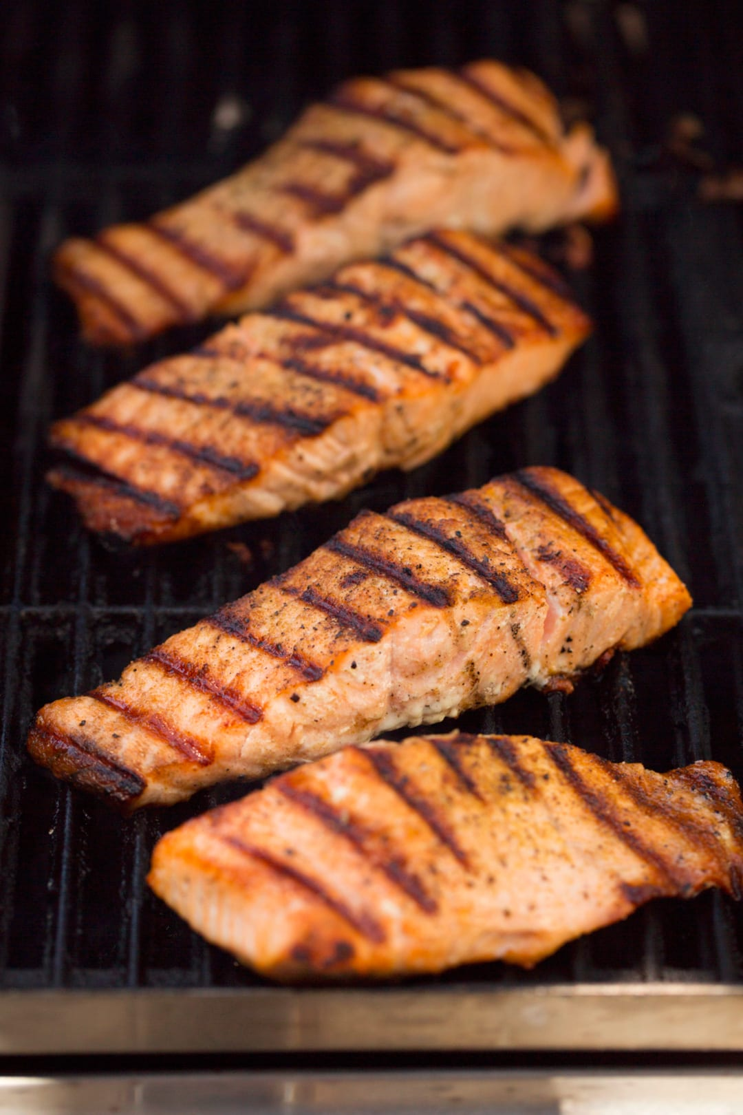 Four salmon fillets pictured here on a grill.