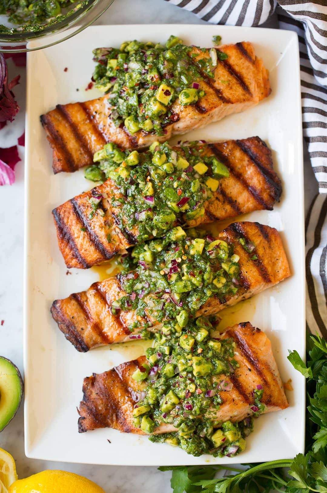 Four grilled salmon fillets on a plate topped with avocado chimichurri.