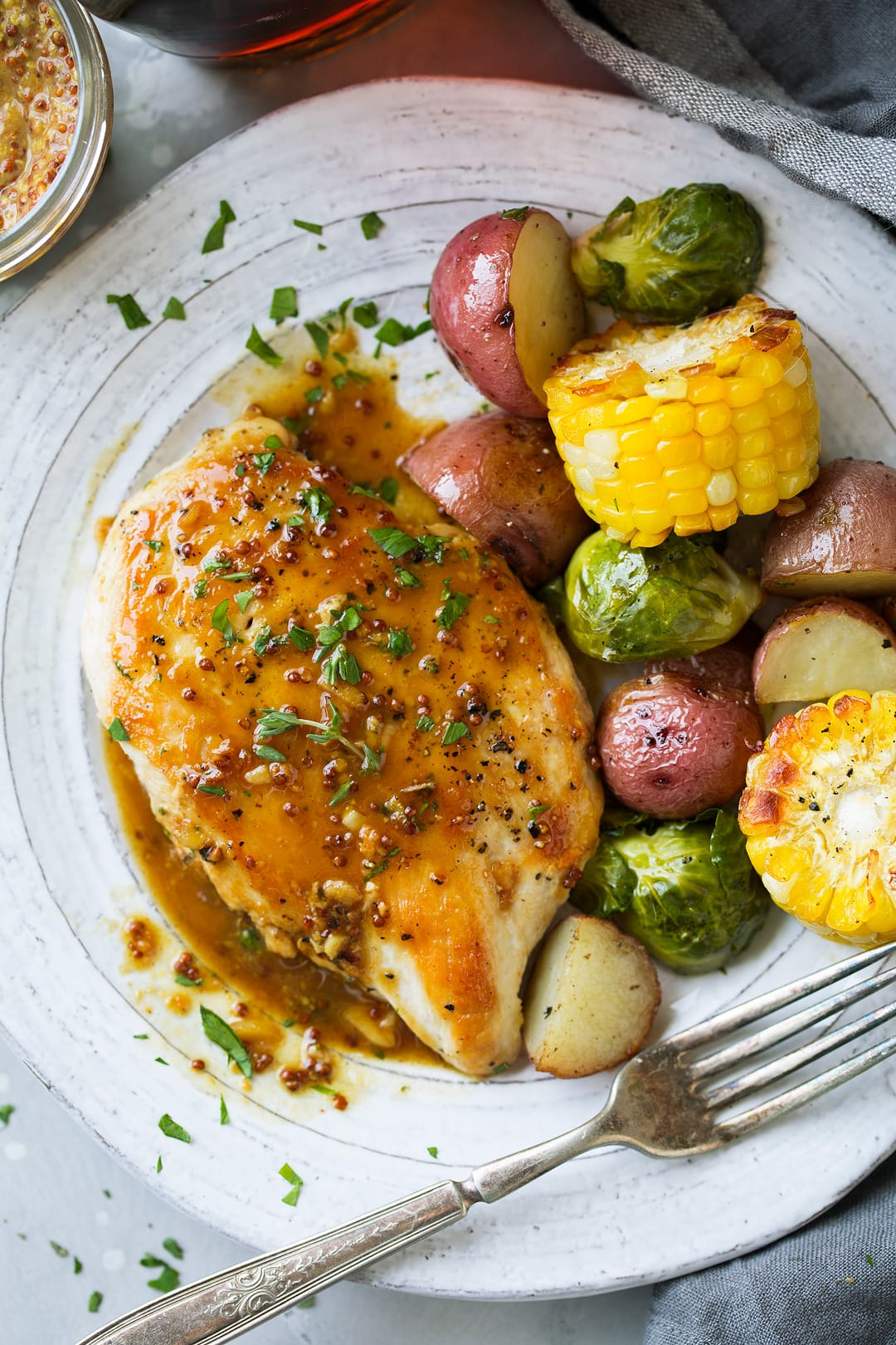 Maple Mustard Skillet Chicken single serving on plate with a side of vegetables.