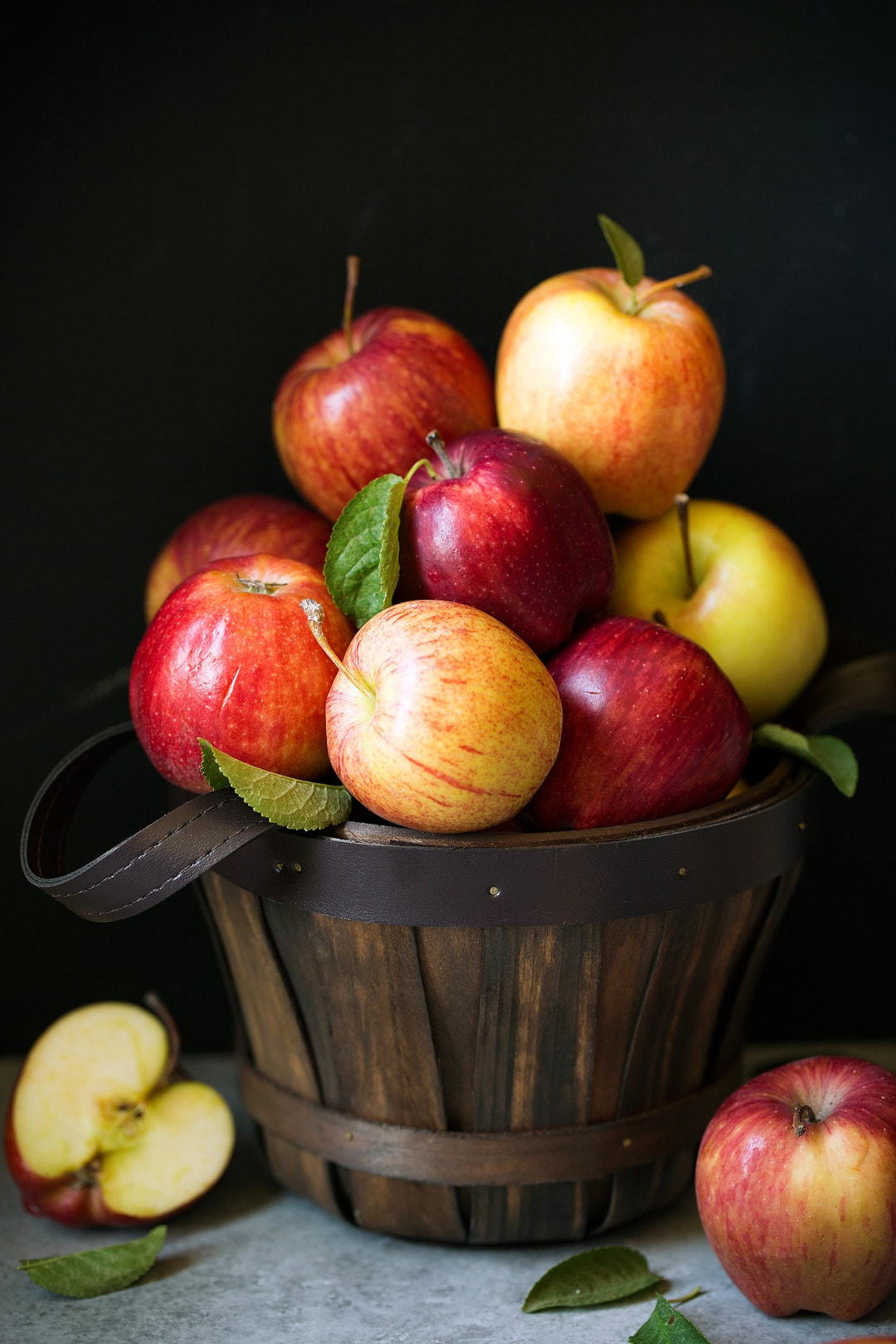 Stack of multi-colored apples in wooden bucket.