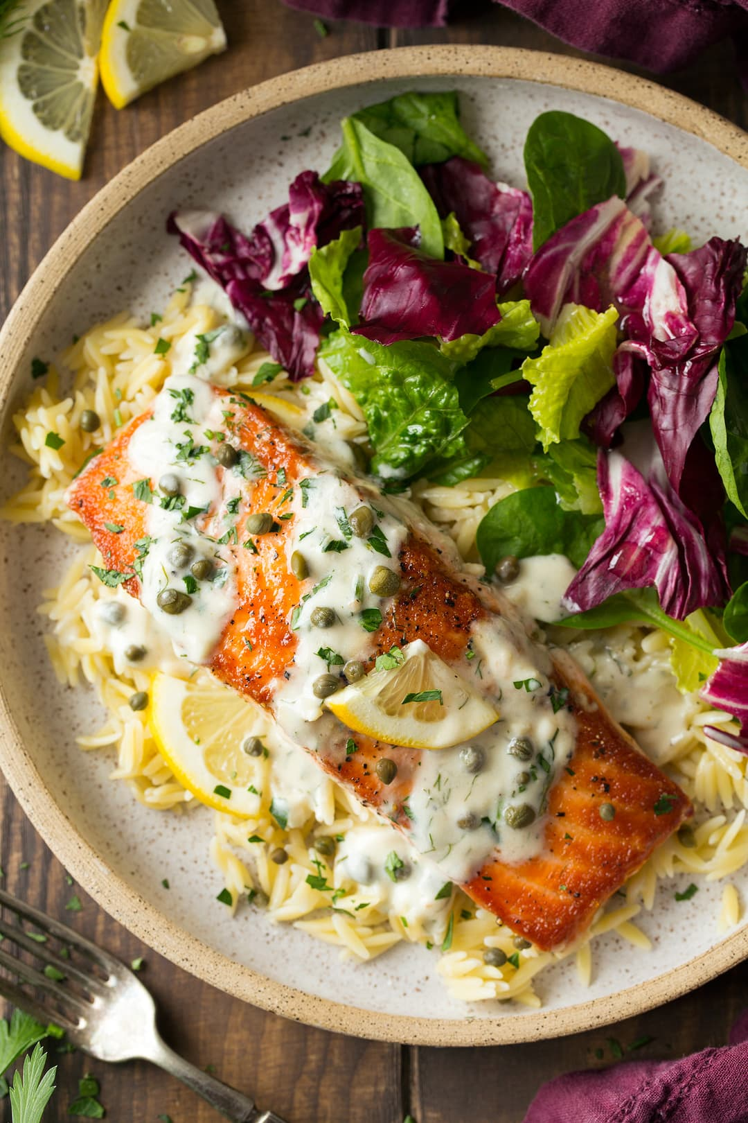 Salmon cooking in skillet with creamy lemon sauce and capers. Shown here on a single serving plate with orzo and a side salad.