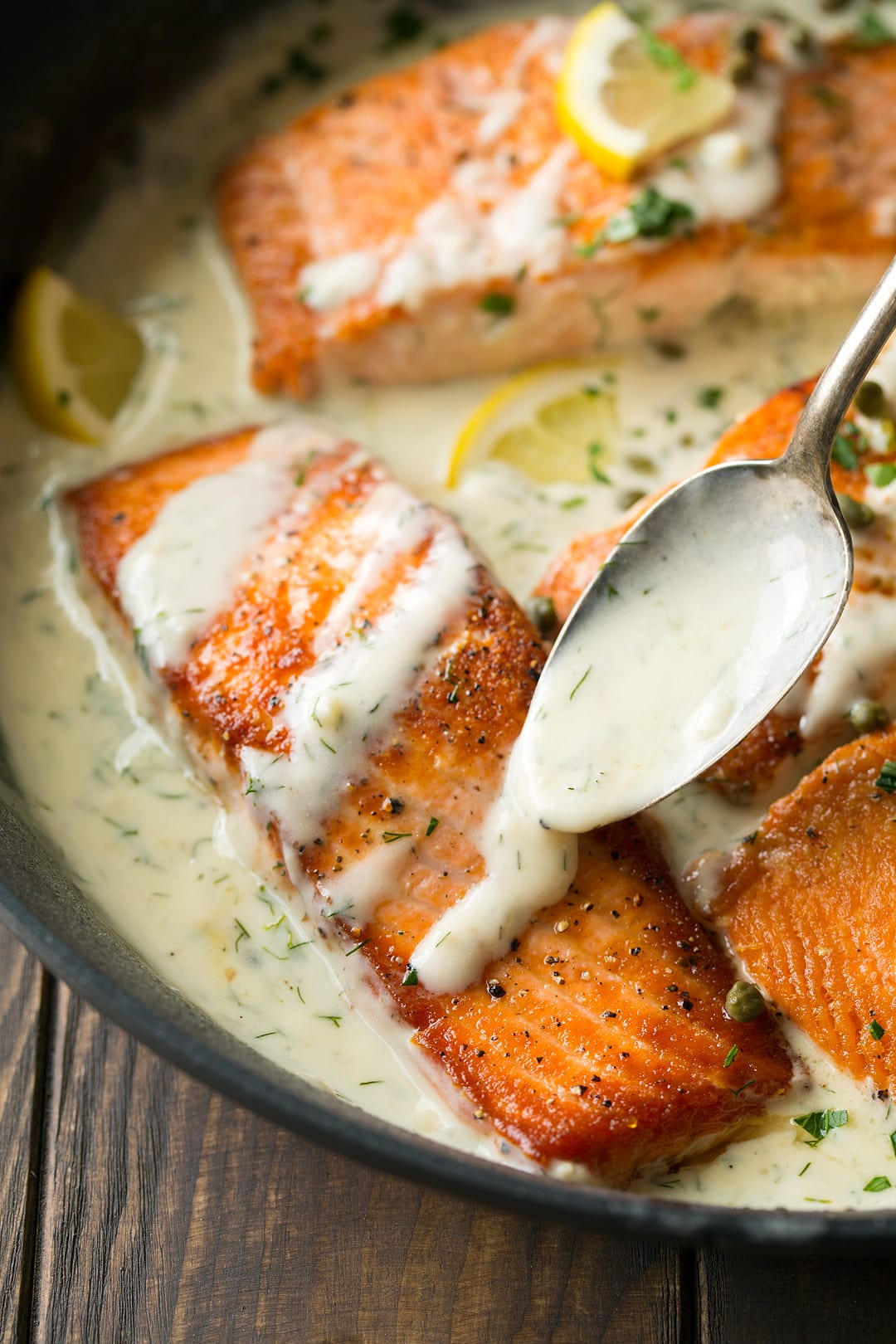 Salmon recipe cooked in a skillet with creamy lemon dill sauce over the top.