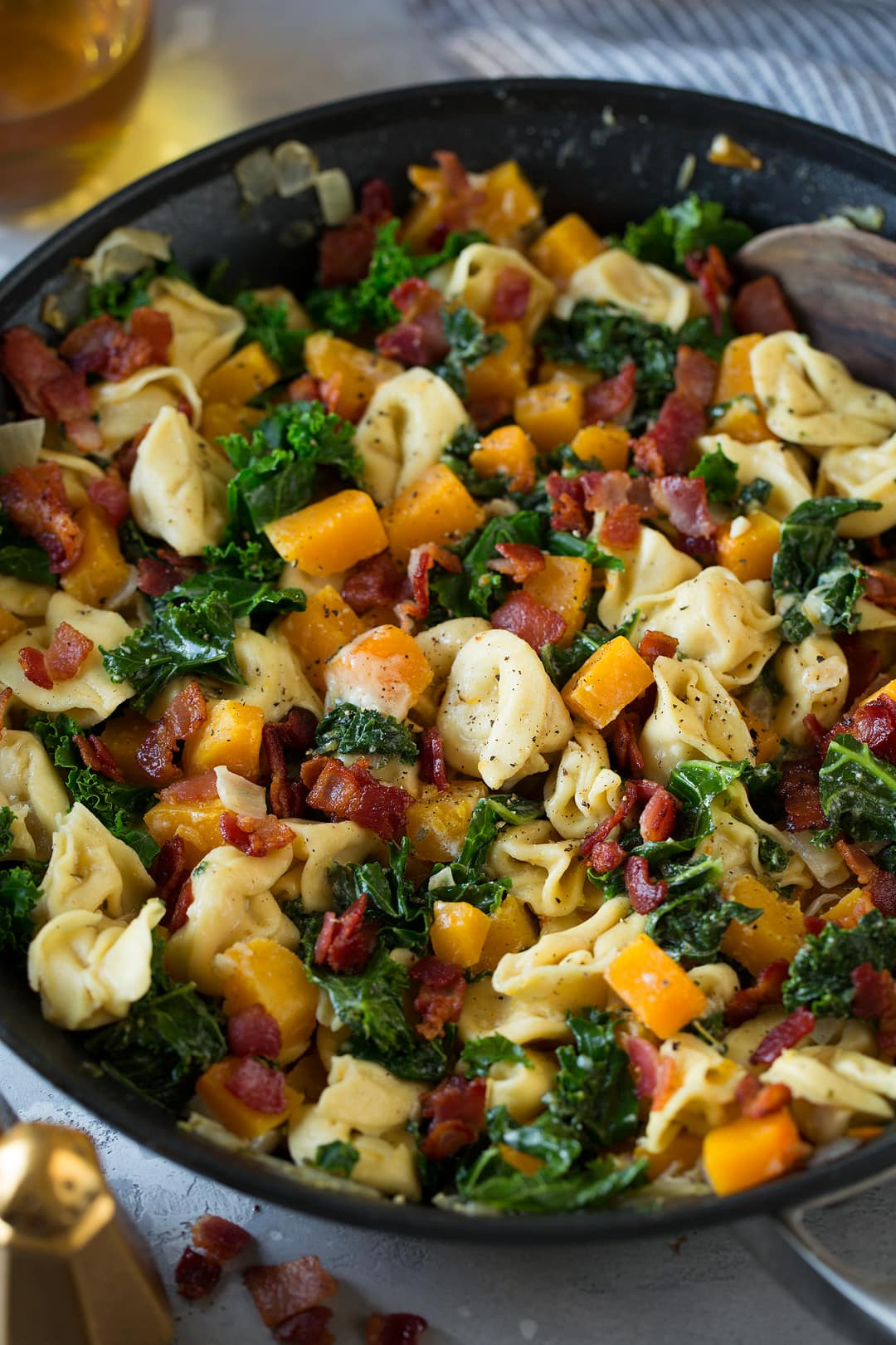 Tortellini with Butternut Squash Kale and Bacon in a large skillet