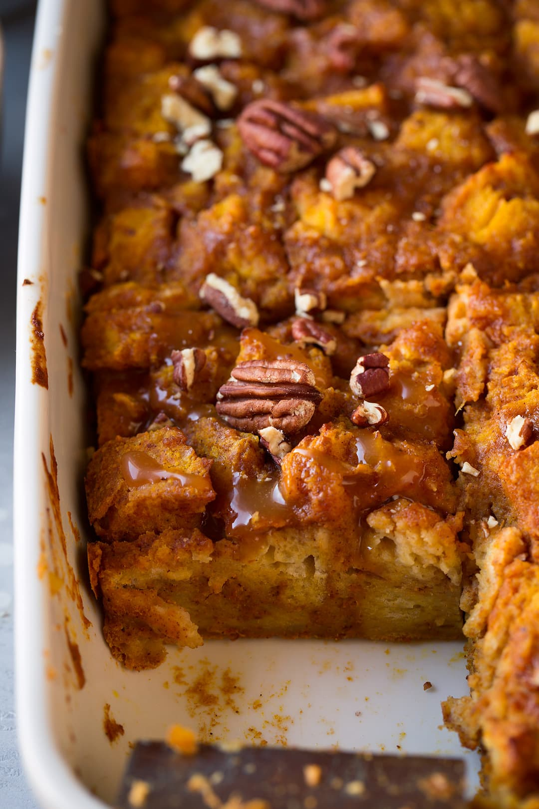 Bread Pudding in baking dish with pumpkin, spices, caramel sauce and pecans.