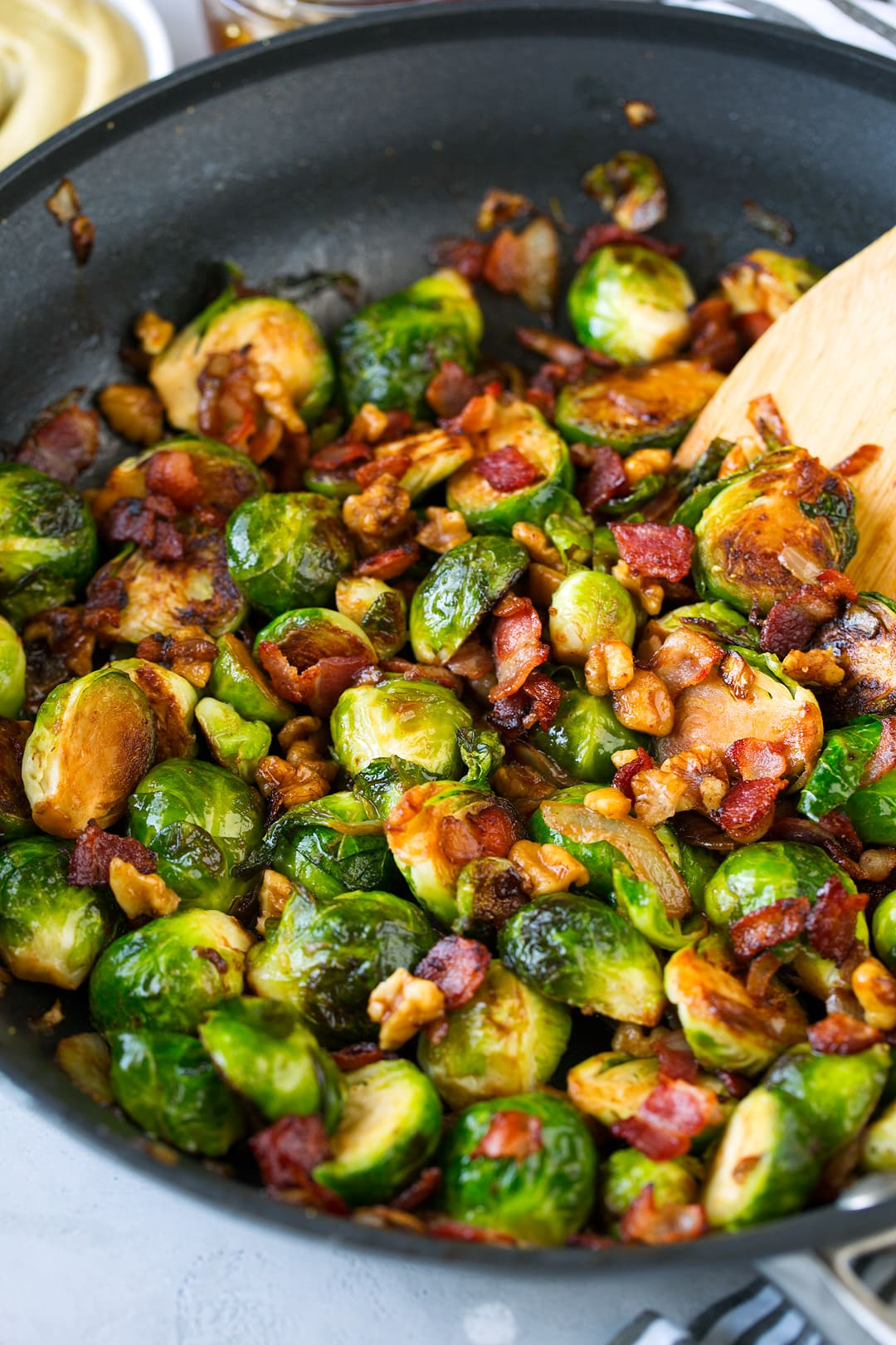 Sauteed Brussels Sprouts with Bacon Onions and Walnuts shown here in a large non-stick skillet