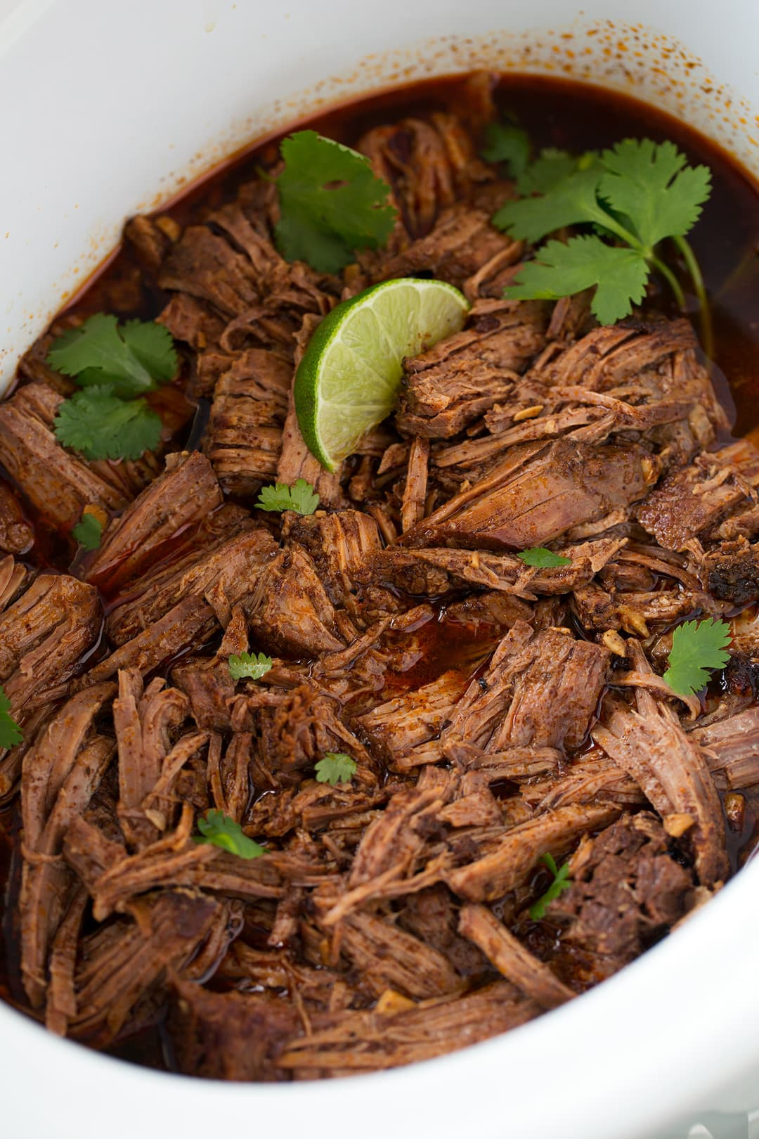 Seasoned taco meat shown here after shredded in a slow cooker