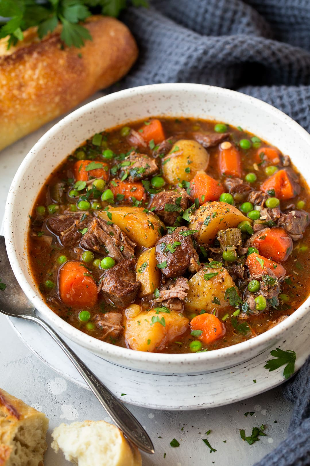 Slow Cooker Beef Stew in a white bowl with bread on the side