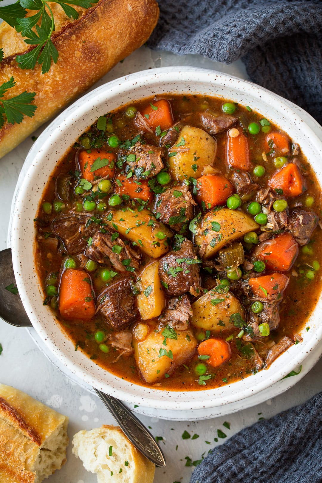 slow cooker Beef Stew shown in a single serving in a white bowl with bread as a side.