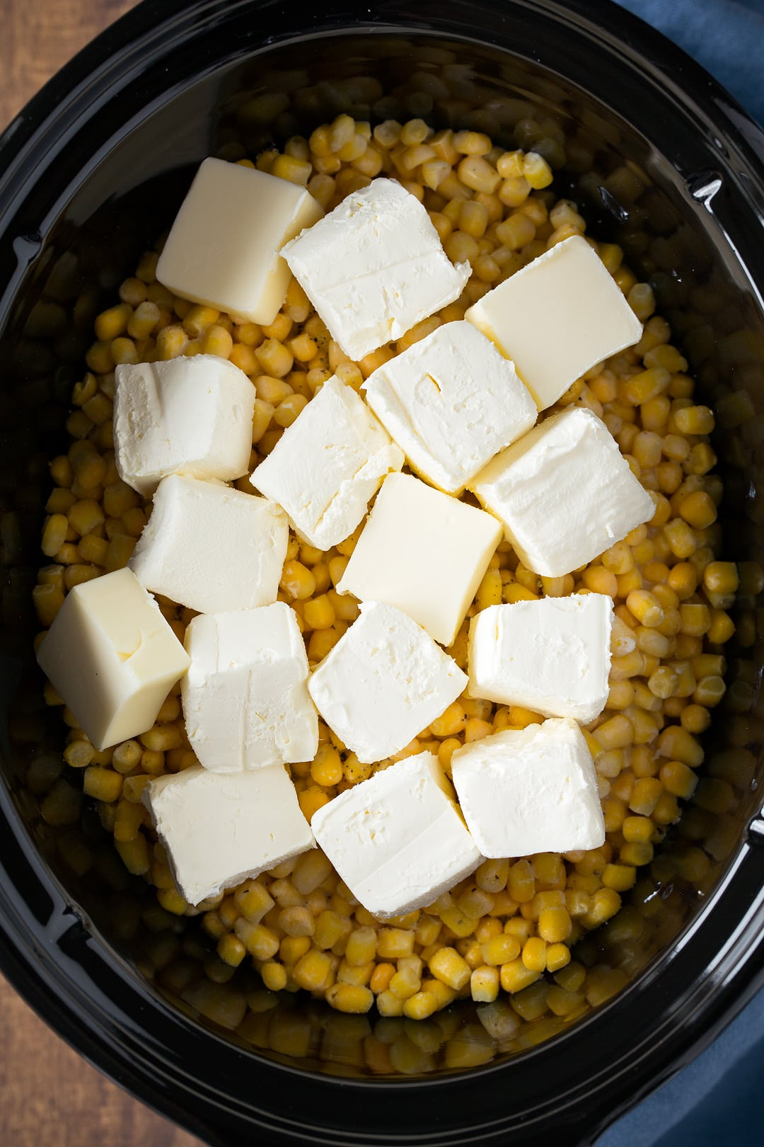 Creamed Corn in a slow cooker. A layer of corn is dotted with cubes of cream cheese before cooking.