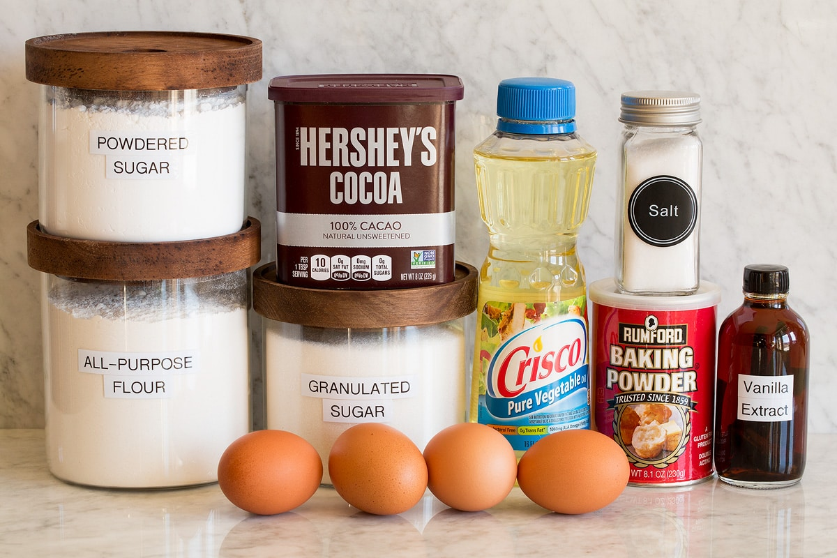 Image of ingredients used to make chocolate crinkle cookies. Includes flour, granulated sugar, powdered sugar, eggs, hershey's cocoa, vegetable oil, baking powder, salt and vanilla extract.
