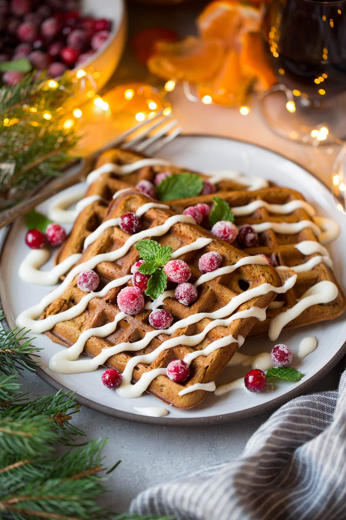 Gingerbread Waffles for Christmas breakfast. Shown here on a serving plate with pine and Christmas lights around waffles.