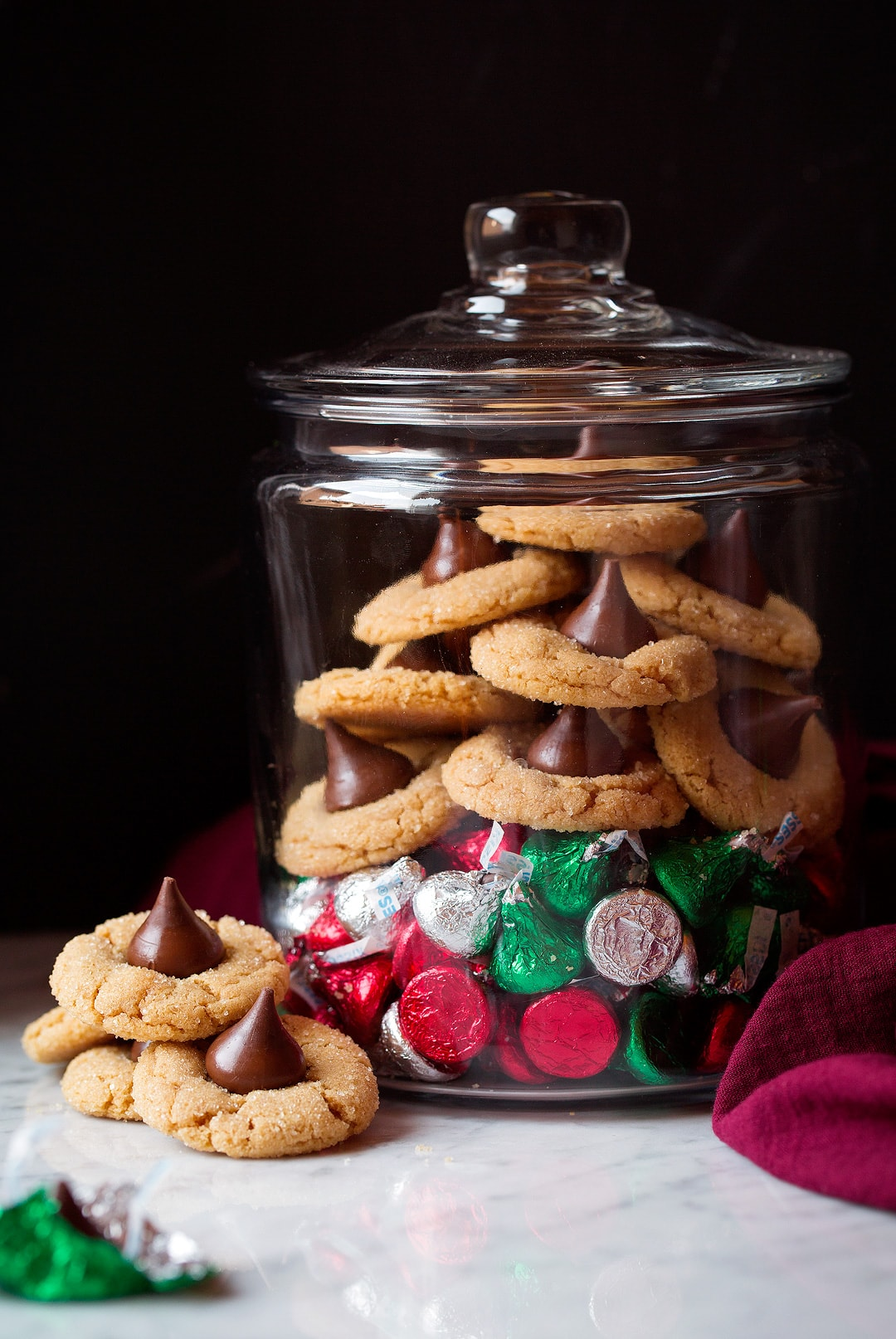 Peanut Butter Blossoms shown here in a clear storage jar over a pile of Hershey's Kisses. Container is set on a marble surface with a black background.