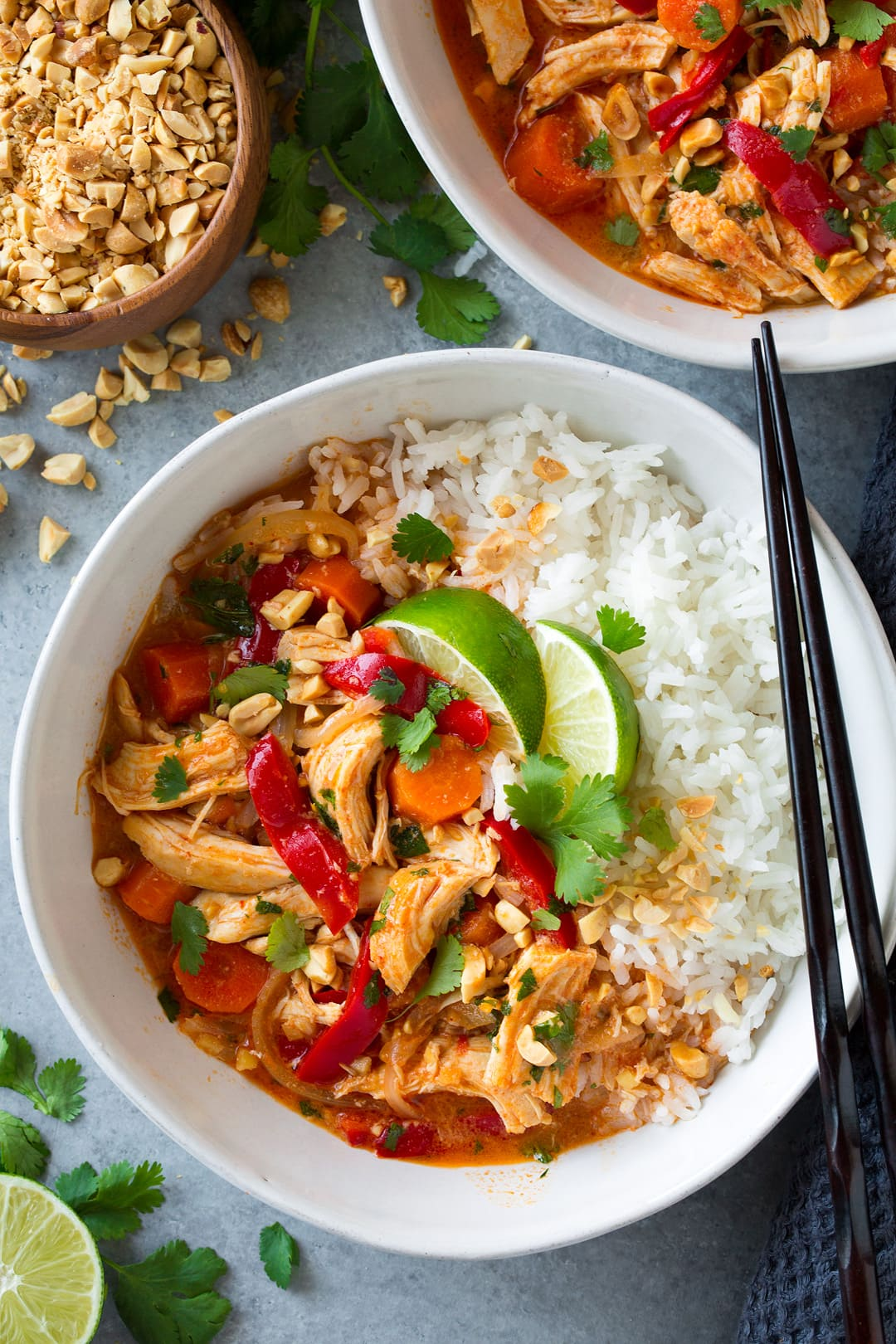 An overhead shot of Slow Cooker Thai Chicken Curry in a white bowl topped with lime wedges