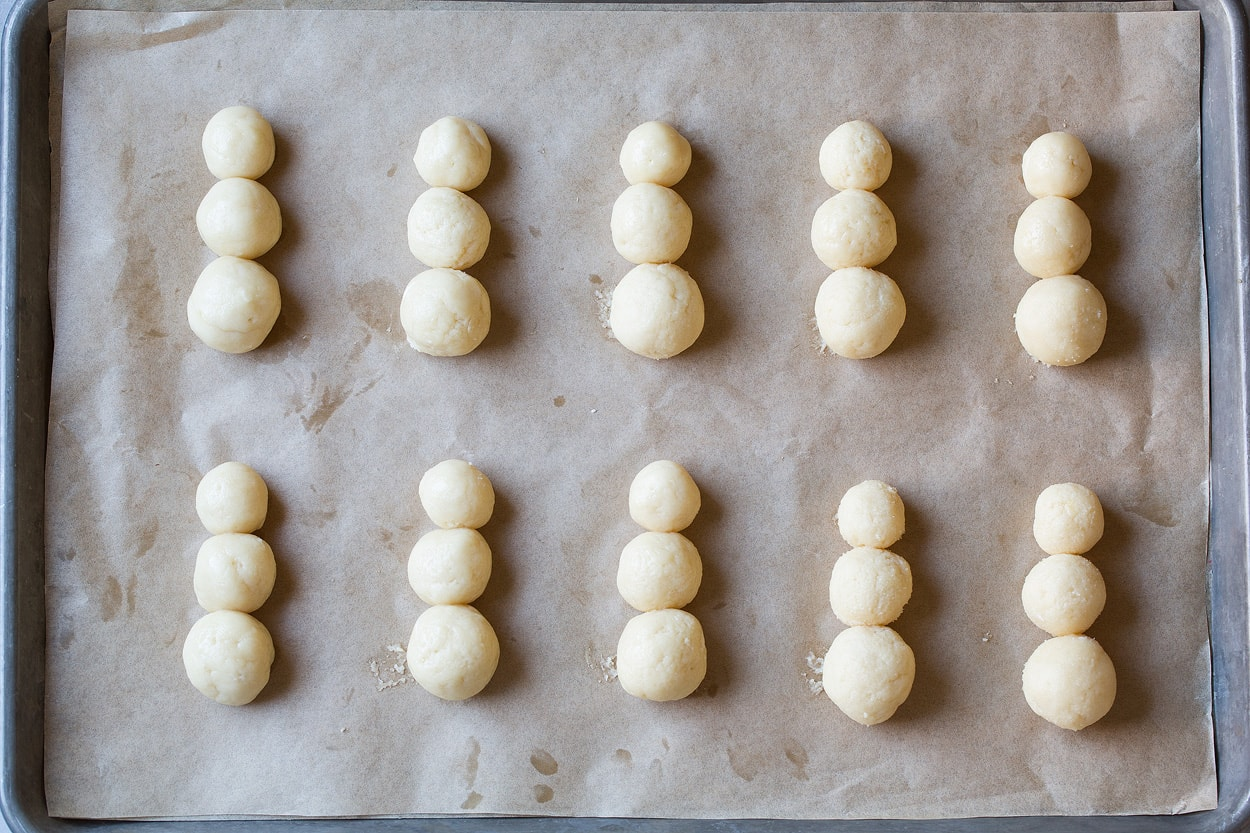 Sugar Cookies shaped into rounds of descending size in stacks of three on baking sheet to make snowman sugar cookies.
