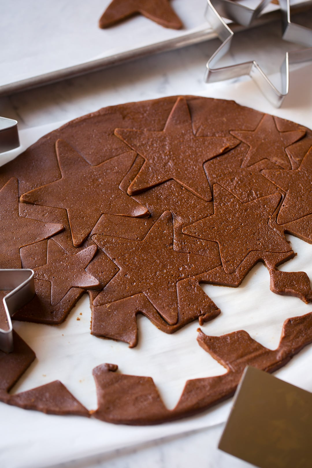 Gingerbread cookie dough cut into star shapes