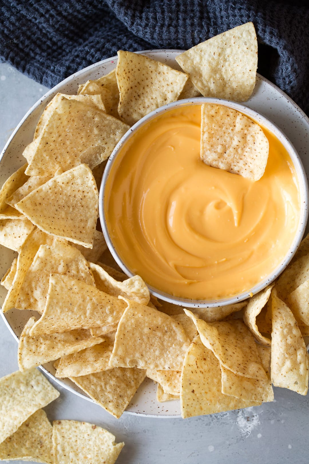 bowl of cheddar cheese dip on a plate with tortilla chips