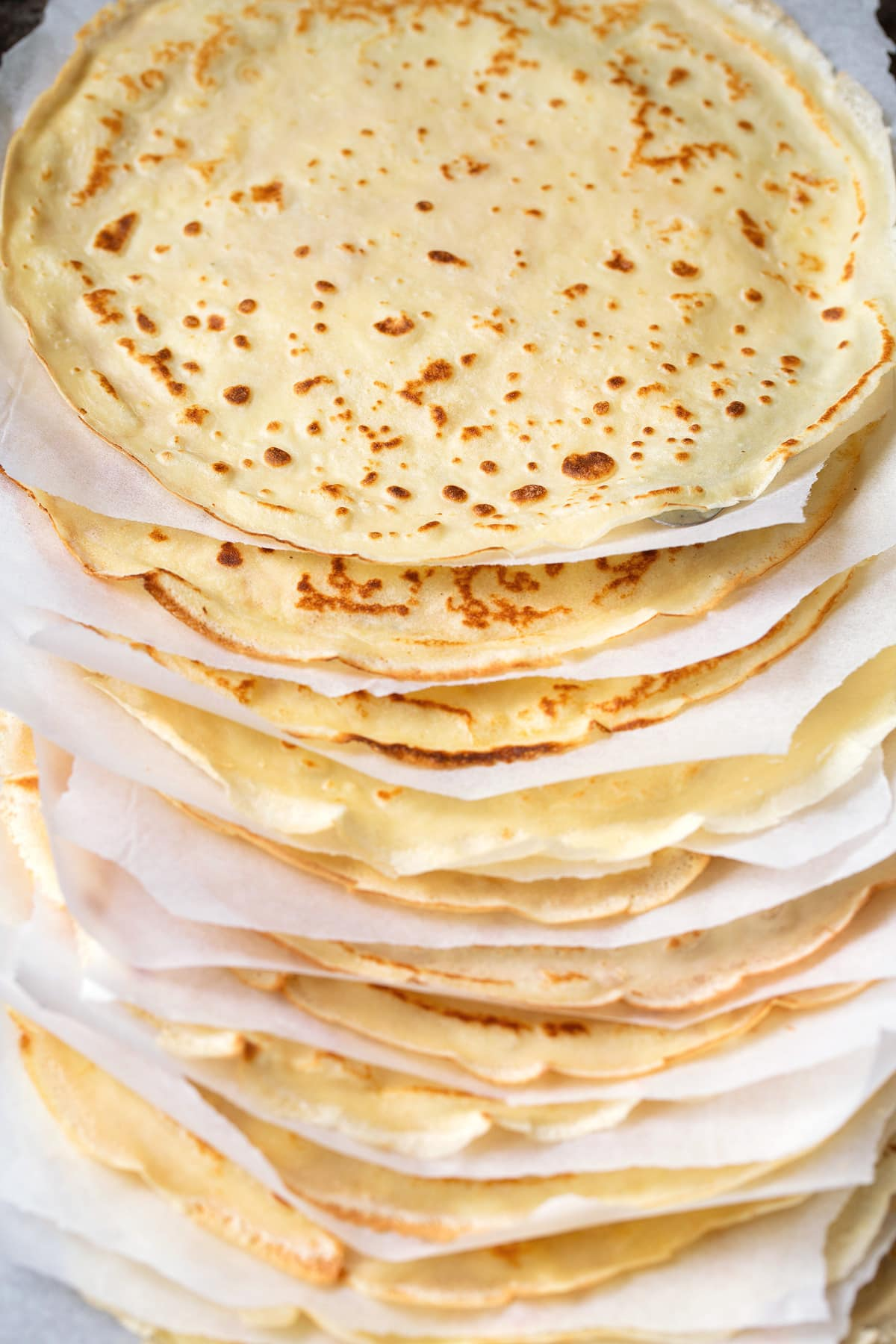 Stack of homemade crepes with parchment paper between each.