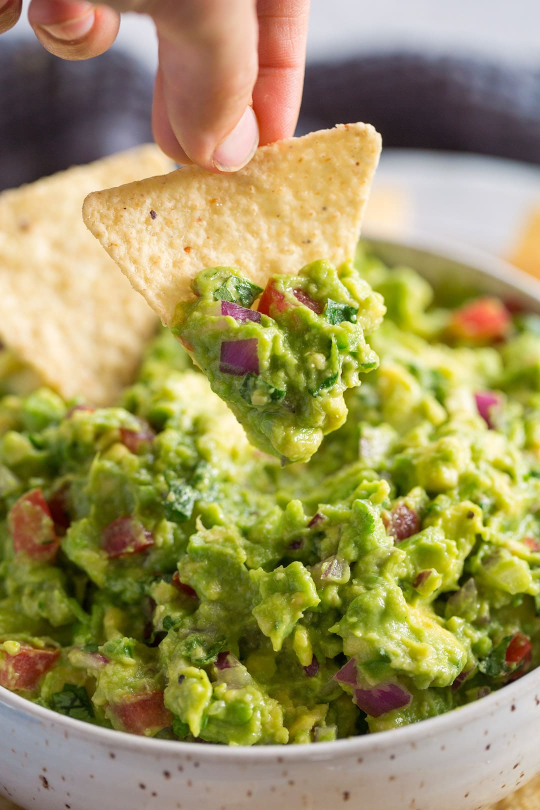 dipping a tortilla chip into fresh guacamole dip
