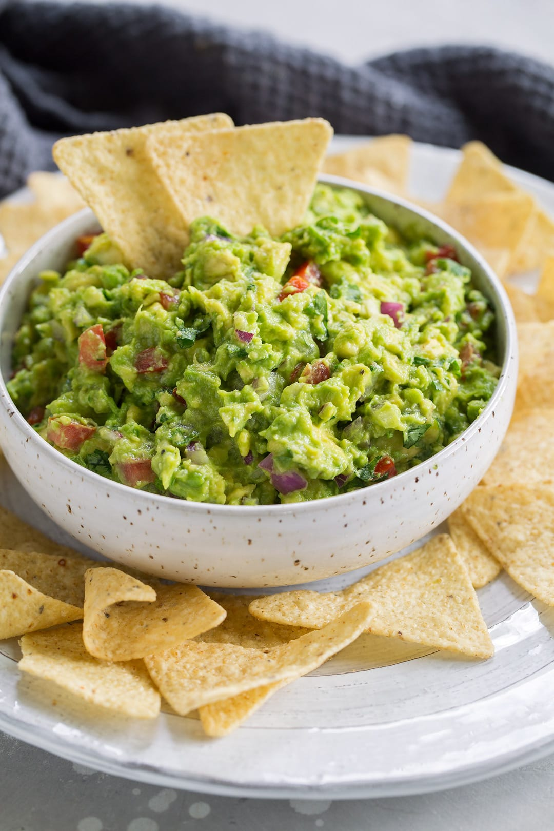 Fresh guacamole in a serving bowl with a side of chips.