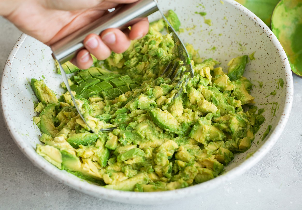 Mashing avocados in a mixing bowl using pastry cutter to make homemade guacamole.