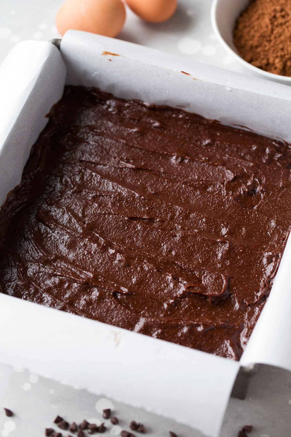 healthy brownie batter in a pan with parchment paper