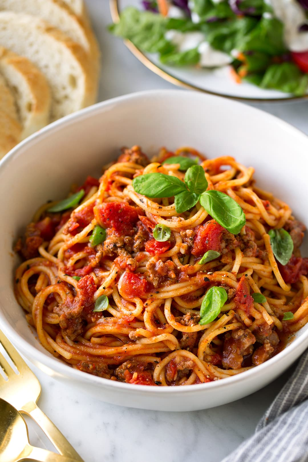 Instant Pot Spaghetti shown here in a single serving in a white pasta bowl with fresh bread and a side salad in the background.
