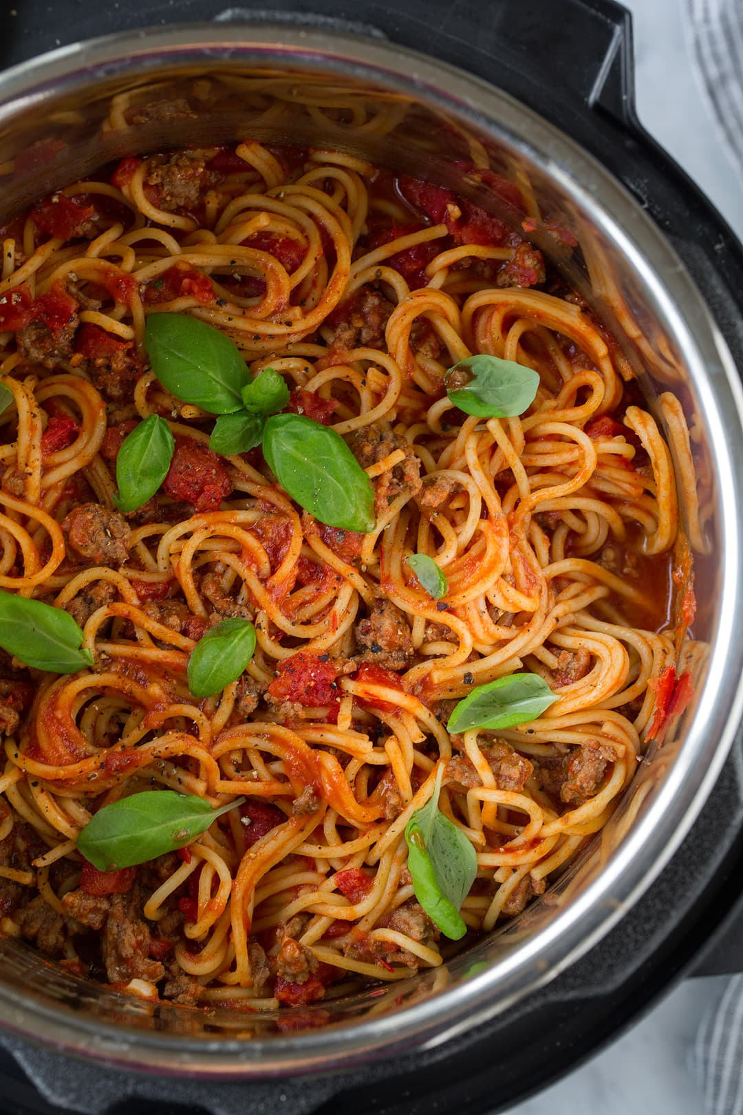 Instant Pot Spaghetti shown here after cooking in the instant pot garnished with fresh basil