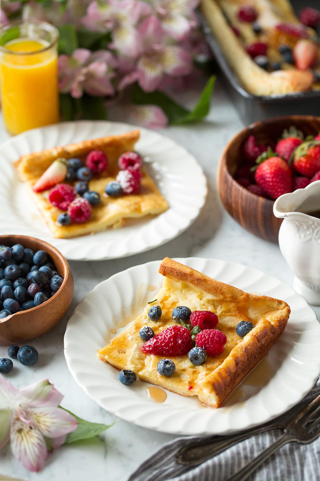 German Pancake slices on white plates with fresh fruit