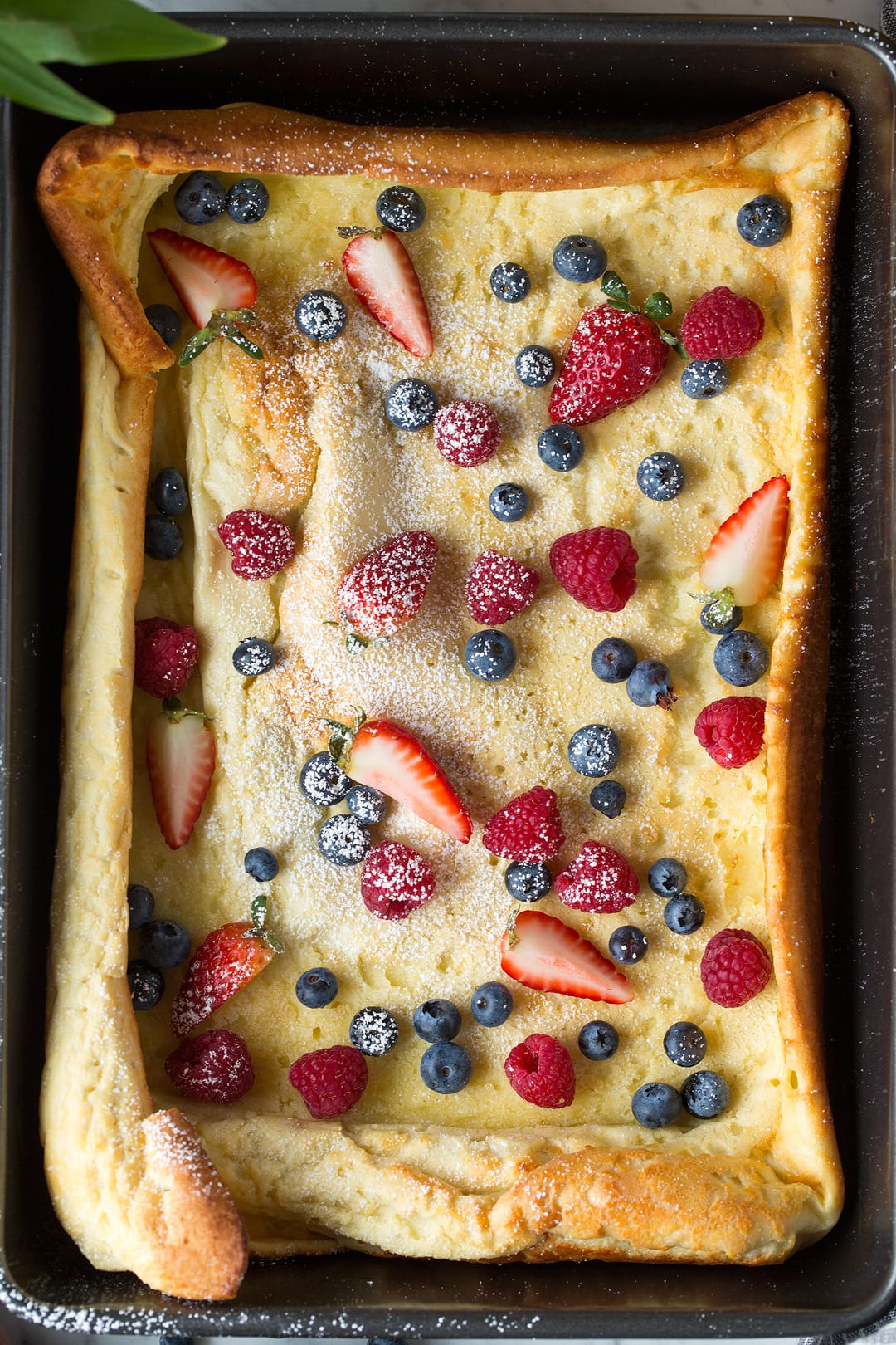 German Pancake in baking pan topped with fresh sliced fruit and powdered sugar