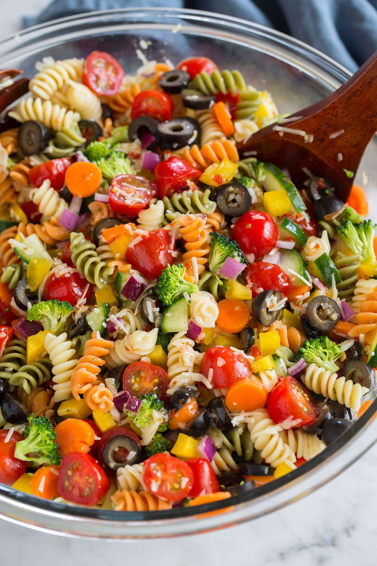 cold pasta salad in a glass bowl with wooden spoon