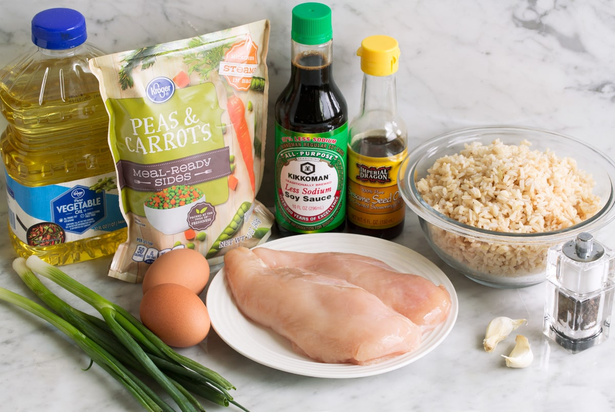 Ingredients needed for chicken fried rice shown here including chicken breasts, brown rice, soy sauce, sesame oil, garlic, eggs, green onions, vegetable oil, frozen peas and carrots.