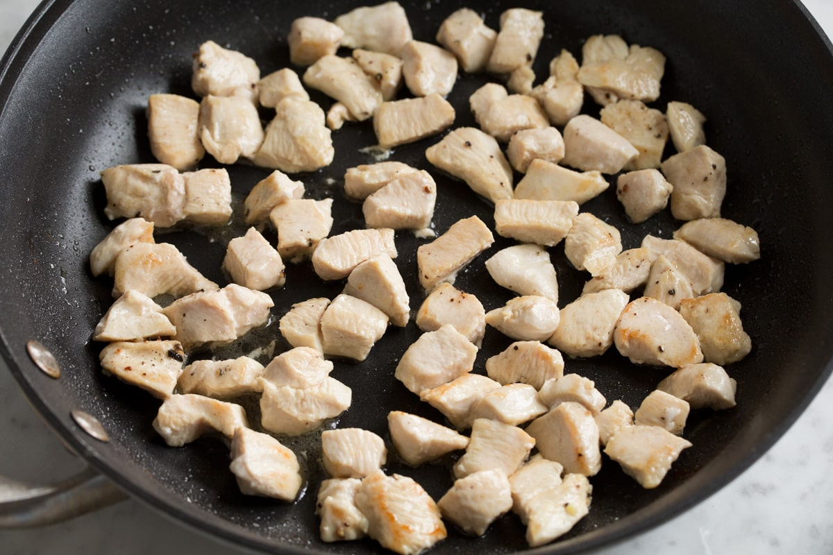 Showing how to make chicken fried rice. Sautéing small chicken breast pieces in a skillet until cooked through.