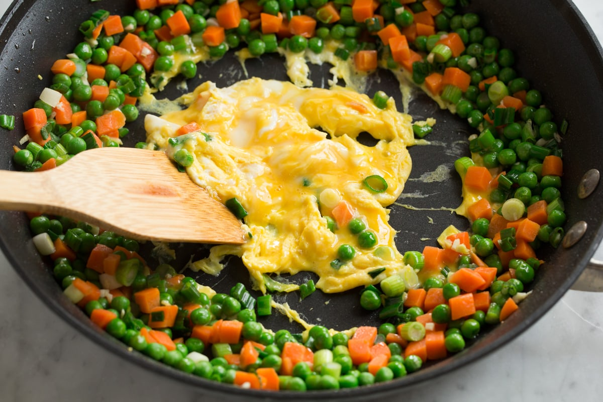 Scrambling eggs in the center of a ring of vegetables in a skillet for chicken fried rice.