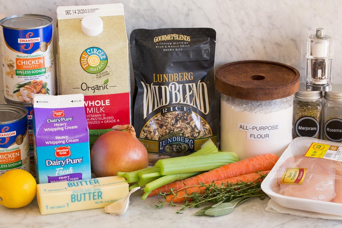 Imagen de ingredientes utilizados para hacer sopa de pollo y arroz salvaje.  Incluye arroz salvaje, pechugas de pollo, hierbas, zanahorias, apio, cebolla, ajo, mantequilla, leche, crema, limón, harina, sal, pimienta y caldo de pollo.