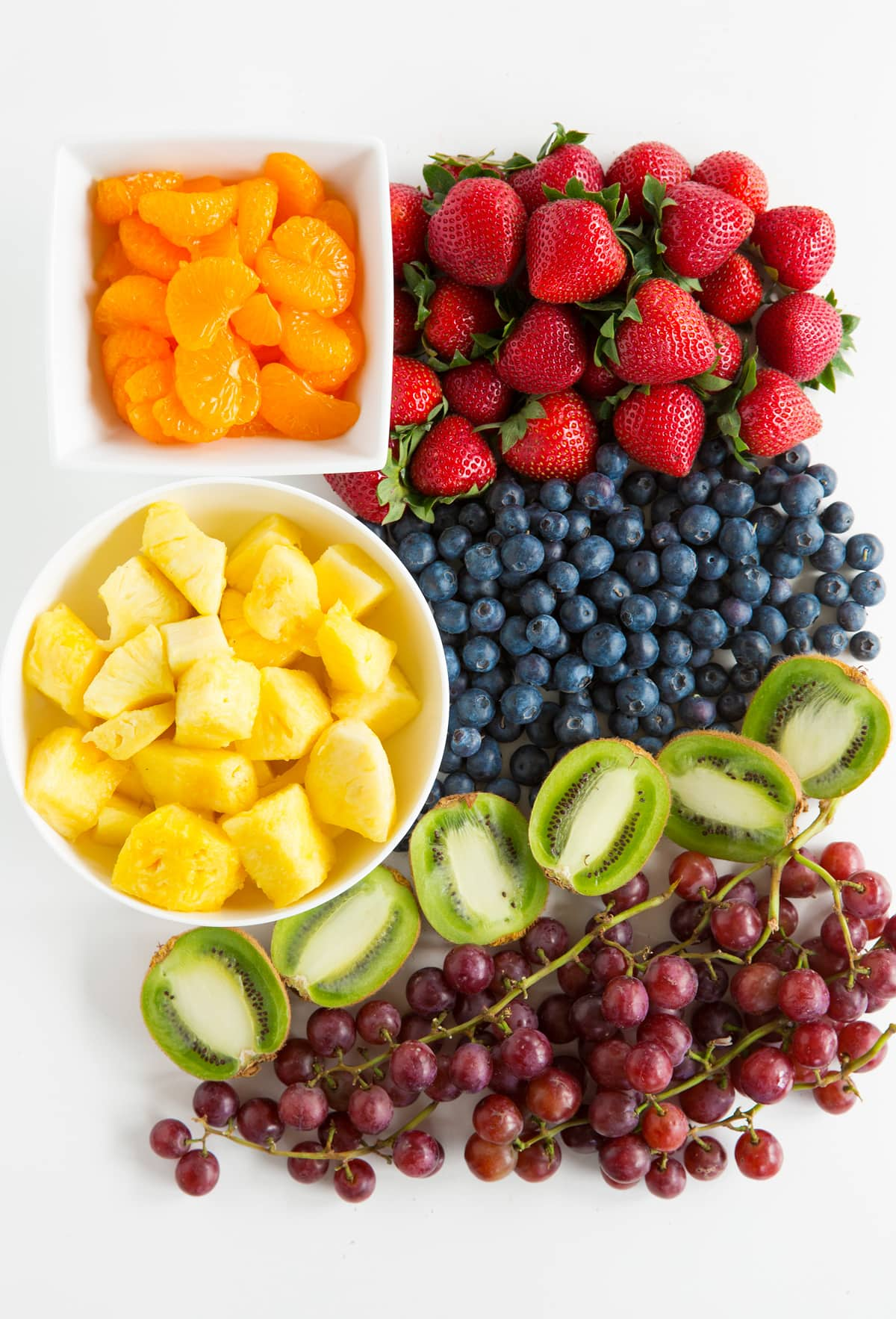 Ingredients needed to make fruit salad shown here including strawberries, blueberries, kiwi, grapes, pineapple and oranges.