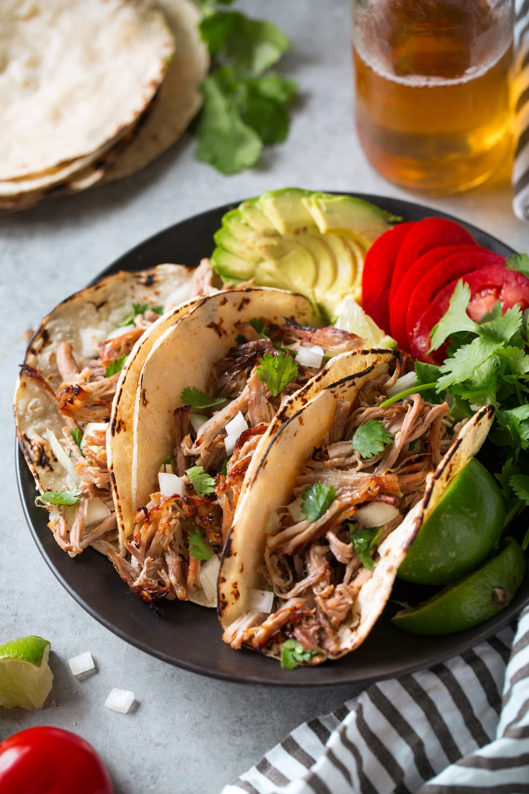 Three carnitas tacos shown here on black a plate in corn tortillas