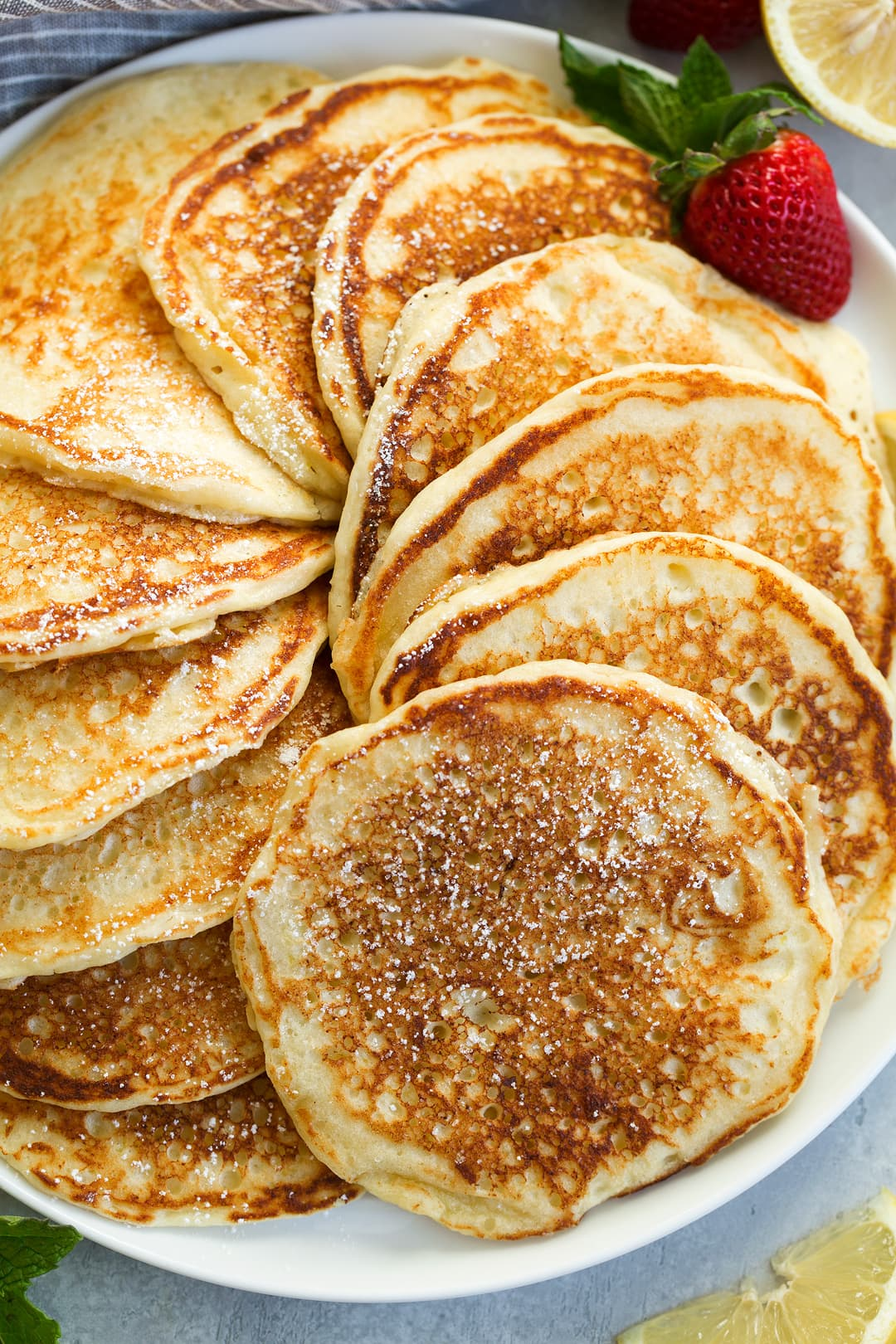stack of lemon ricotta pancakes swirled around on a large plate garnished with lemon slices and strawberries