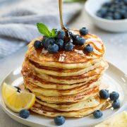 stack of eight lemon ricotta pancakes topped with fresh blueberries and mint maple syrup poured over pancakes lemon slices added on plate for garnish
