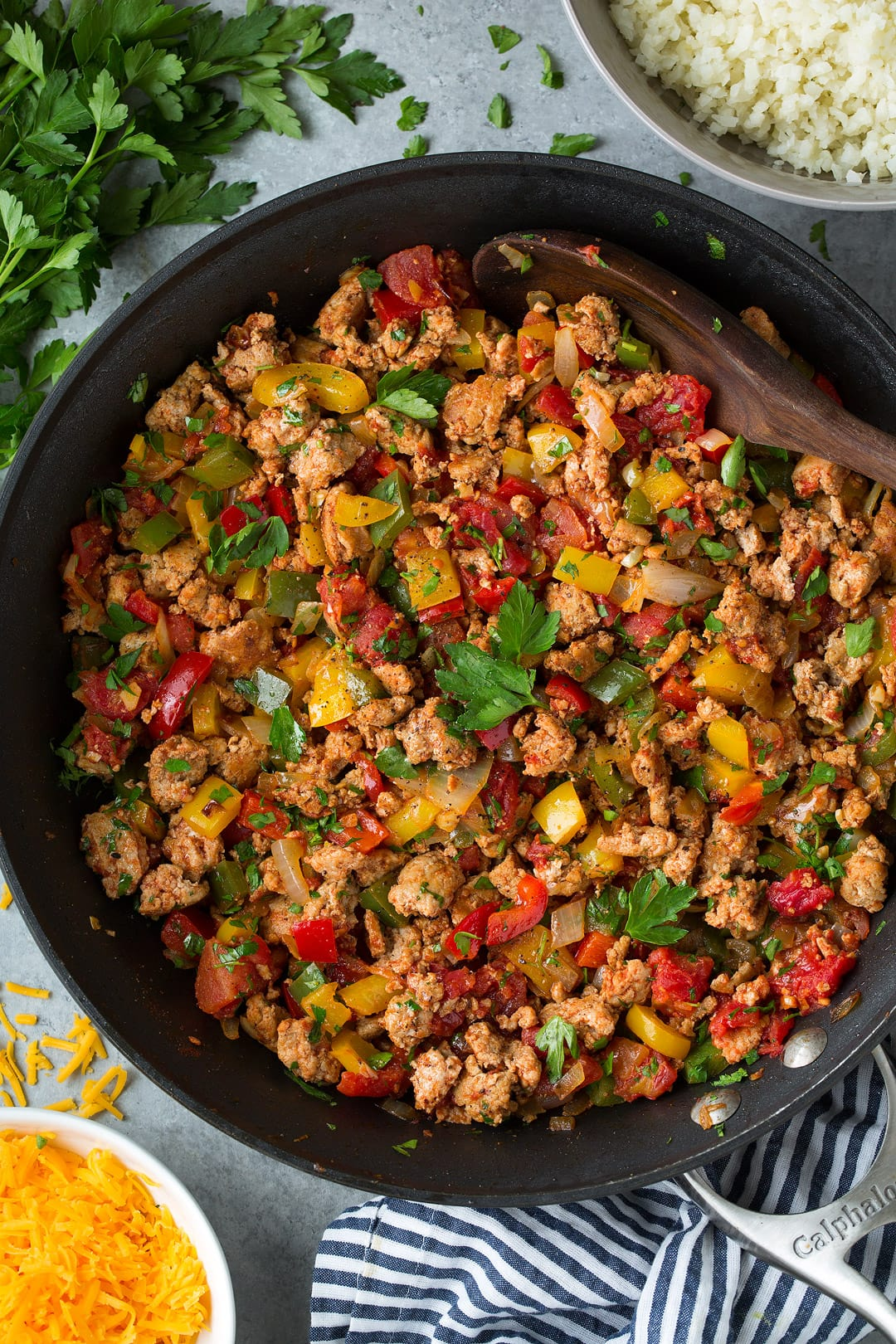 Unstuffed Pepper mixture of ground turkey, peppers and parsley shown here in a dark skillet on a grey surface