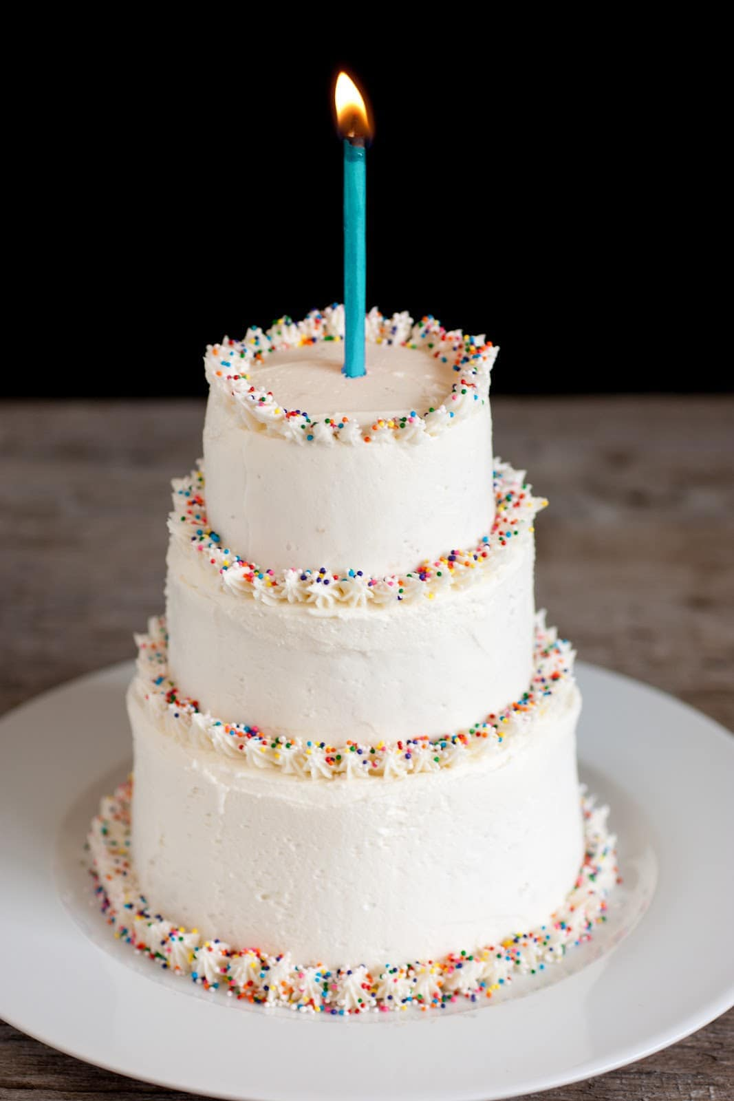Three tiered cake covered with the best vanilla buttercream frosting. Cake edges are garnished with multi colored sprinkles and there's one lit candle atop the cake.
