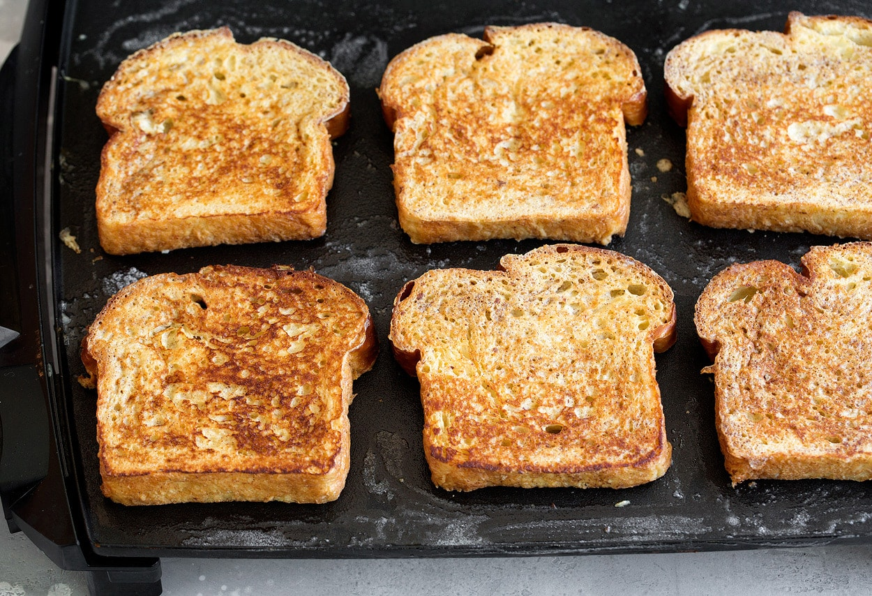six slices of french toast cooking on electric griddle