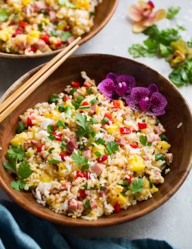 Wooden bowl full of hawaiian fried rice decorated with flowers and chopsticks to the side.