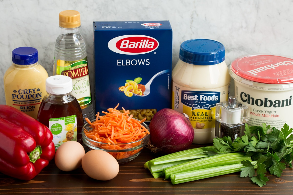 Ingredients that are in macaroni salad shown here. Includes mayonnaise, Greek yogurt, dijon mustard, honey, eggs, carrots, bell pepper, celery, parsley, vinegar, salt and pepper.