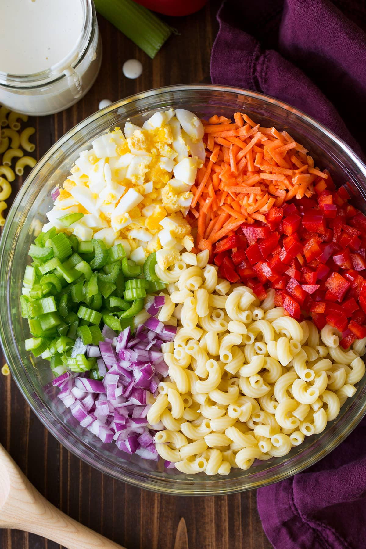 Macaroni salad ingredients in a glass bowl before tossing together.